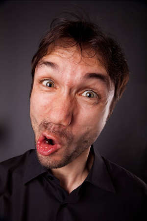 closeup portrait of grimacing man in black shirt