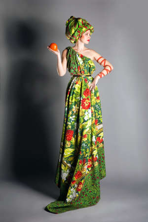 portrait of a woman in a green dress with a turban on his head and his fruit in his hand Stock Photo