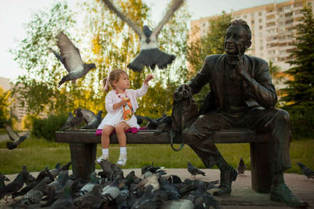 a little girl feeding the pigeons in the park near the statue photo