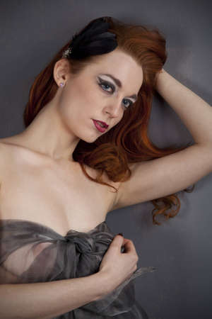 Redhead girl in a dress of black transparent fabric posing in studio Stock Photo