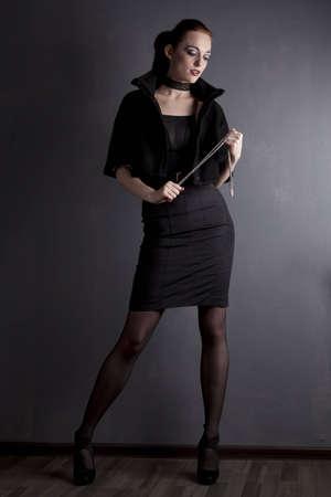 Redhead young girl in black dress posing in studio Stock Photo