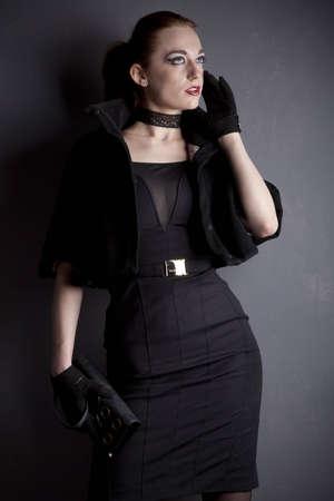Redhead young girl in black dress posing in studio Editorial