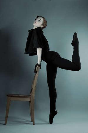 performs: giovane ballerina esegue esercizi vicino alla sedia