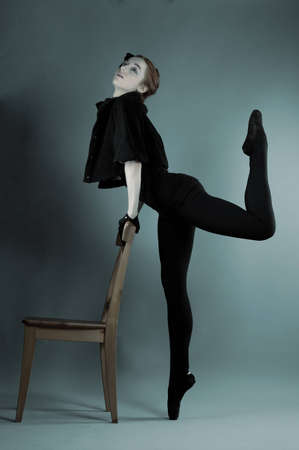 young ballerina performs exercises near the chair