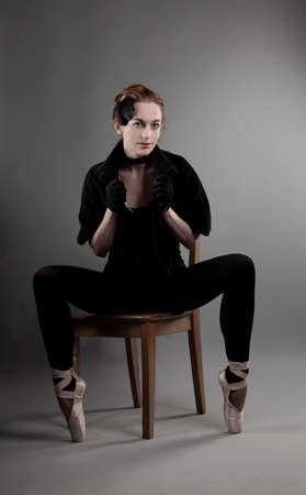 young ballerina performs exercises near the chair photo