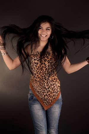 portrait of a very beautiful brunette girl in leopard tunic posing in studio photo