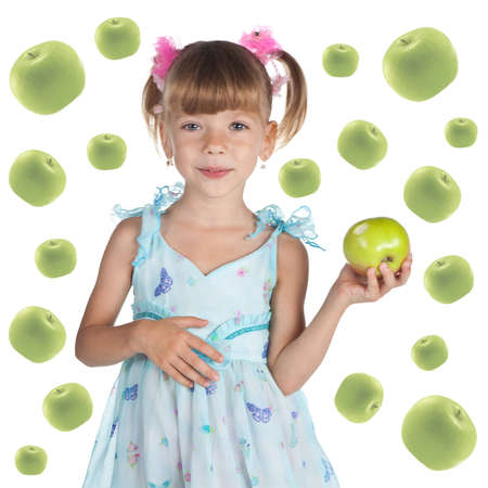 Portrait of a cute little girl in a blue dress with a fresh green apple on the white photo