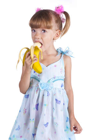 Pretty little girl in a blue dress with a banana in her hands photo