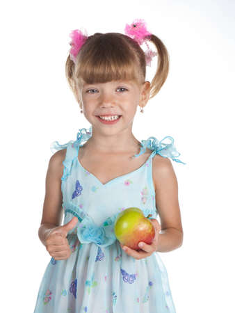 Pretty little girl in a blue dress with an apple in her hand