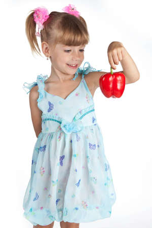 a little sweet girl with a sweet red pepper in her hand