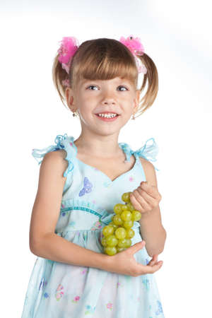 Pretty little girl with green grapes in her hand on the white Stock Photo