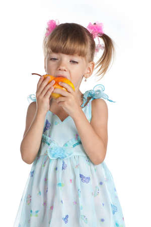 Pretty little girl with a juicy pear on the white