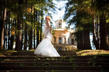 Bride in white dress on a clear warm day, posing on the stairs