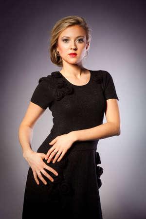 portrait of a beautiful blonde girls in black dress in studio