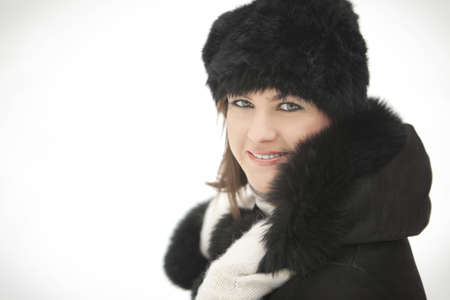 girl in a fur hat and sheepskin coat smiles photo