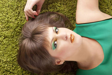 girl in green dress on a background of light green rug photo