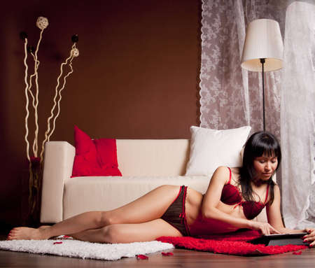 girl in red swimsuit lying on the rug, and read Stock Photo - 12685224