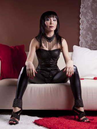 girl in a slinky black dress posing on a light couch in the studio