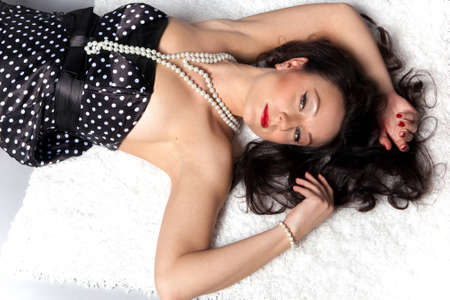portrait of a girl lying on a light carpet with bare shoulders photo