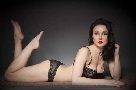 beautiful girl in underwear lying in the studio and posing photo