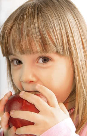 put forward: little girl with large gray eyes bite the apple