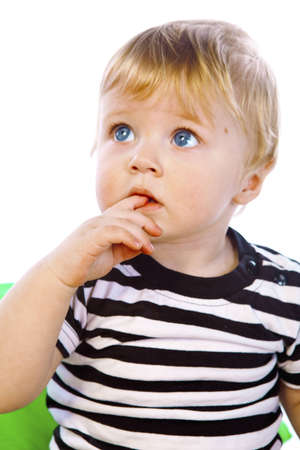 a little boy in the striped shirt, holding his finger in his mouth, close-up, in the studio