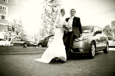 couple in love, the bride and groom standing near a car photo