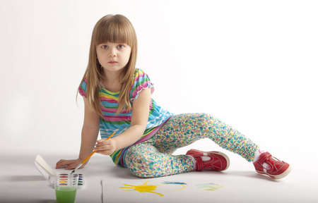 little girl in a dress the color paints paints sitting on the floor Stock Photo - 13066011