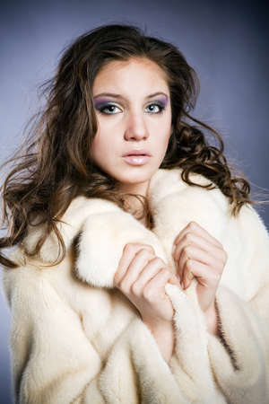 beautiful young woman; blue eyes; brown hair; a white fur coat photo