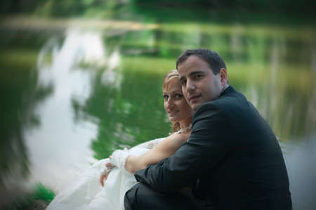 young couple sitting by the river Stock Photo