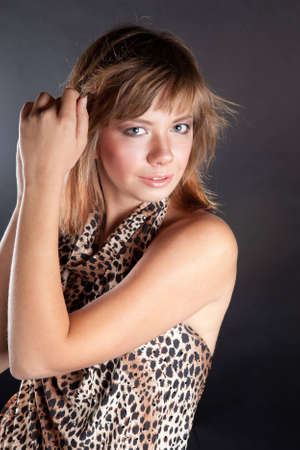brown-haired girl dressed in a tiger, leopard fabric poses in the studio photo
