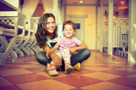 Girl sitting at the foot of a young woman, both happy