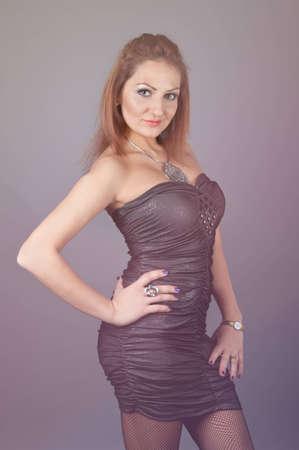 young woman in black dress posing in studio Stock Photo
