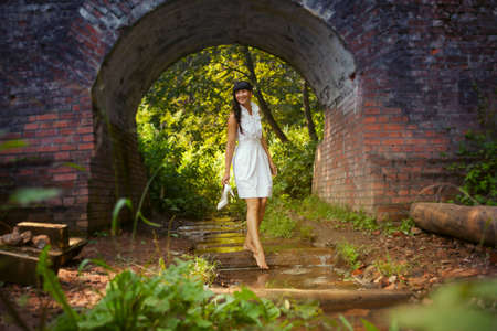 young woman standing in the water against a brick arch photo