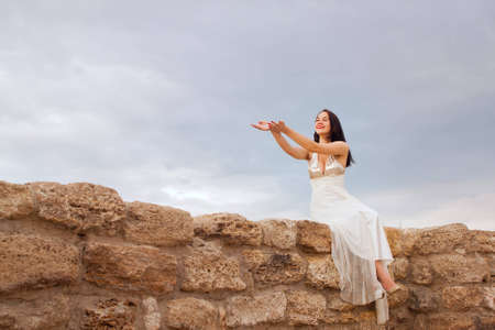 A young woman dressed in white against the sky Stock Photo