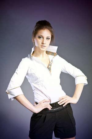 beautiful young woman; blue eyes; brown hair; black shorts; white shirt photo