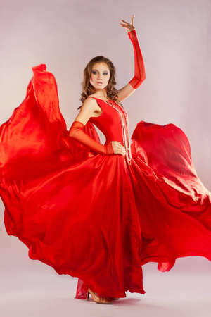 young woman in a bright red dress posing in studio Stock Photo