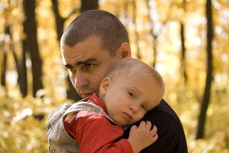 ni�os tristes: Joven toma su peque�o hijo en sus brazos en el oto�o de parque Foto de archivo