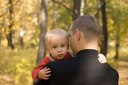 Young man takes his crying son in his arm in autumn park photo