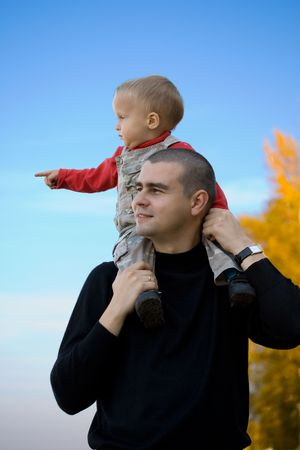 Adorable little boy sitting on his fathers shoulders over blue sky photo