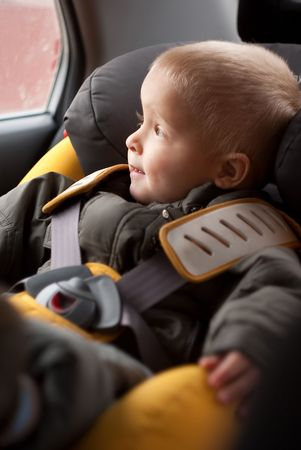 enfant banc: Adorable petit gar�on assis dans le carseat de s�curit�