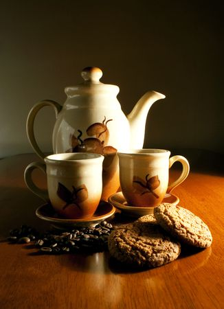 coffeepot: Coffeepot with two cups of coffee and cookies