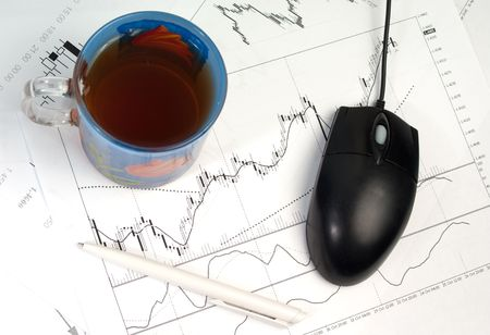 computer mouse, cup of tea and pen over exchange graphs photo