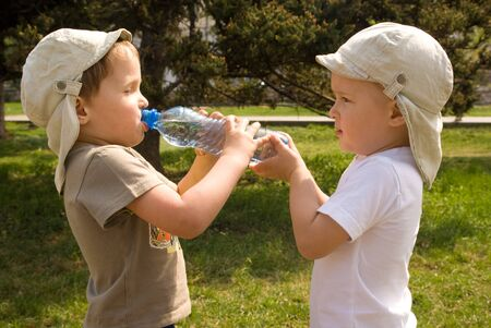 Two little boys drinking water from the bottle outdoor Stock Photo - 7094124