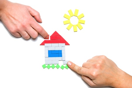 Male and female hands building toy house Stock Photo - 11184714