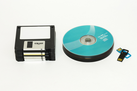 On a white background are Floppy, CD  DVD disk and USB flash