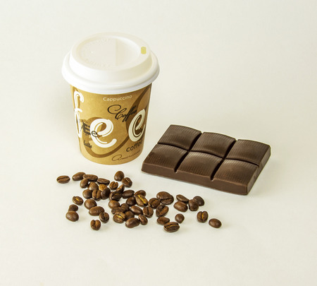 On a gray background is a paper cup of coffee, lying tiles of dark chocolate and coffee beans scattered