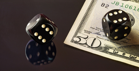 On the mirror surface reflects the black dice to play poker and is a banknote fifty dollars. Stock Photo