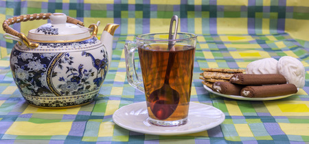 On the table is a glass cup with tea, tea and sweets in the basket are