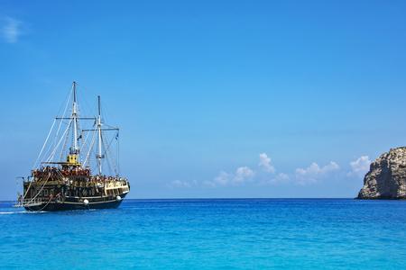 Zakynthos Island, Greece - 09062016: Tourists on a seagoing vessel, stylized old ship sailing on the sea